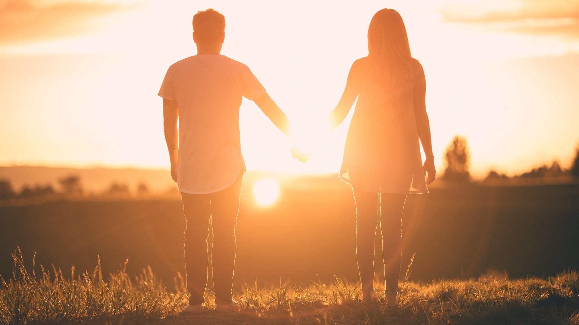 夕焼け空をみつめる2人の画像