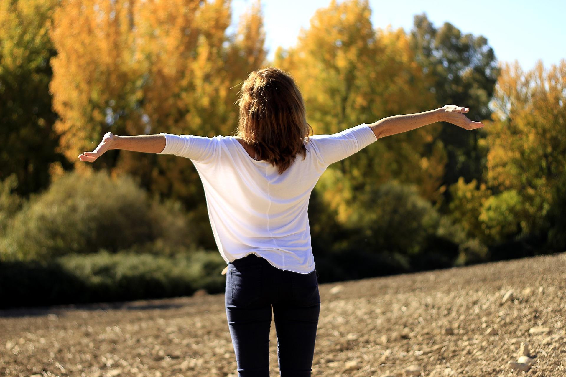 両手を広げのびする女性の画像